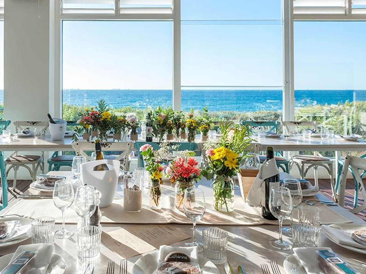 A Table Set Up With Flowers And A View Of The Ocean.