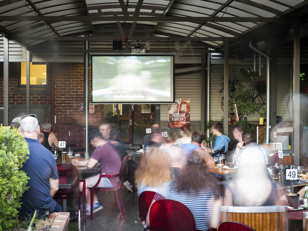 Outside Function Area with People Sitting with TV Screen