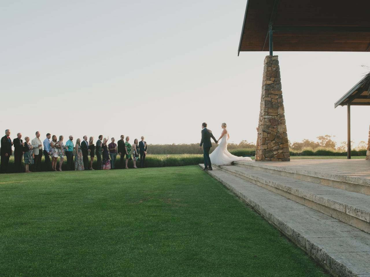 Bride and bridegroom walking across grass at venue
