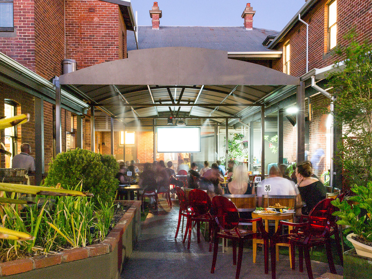 Garden Bar with People Sitting in Banquet Style with TV Screen in Dusk