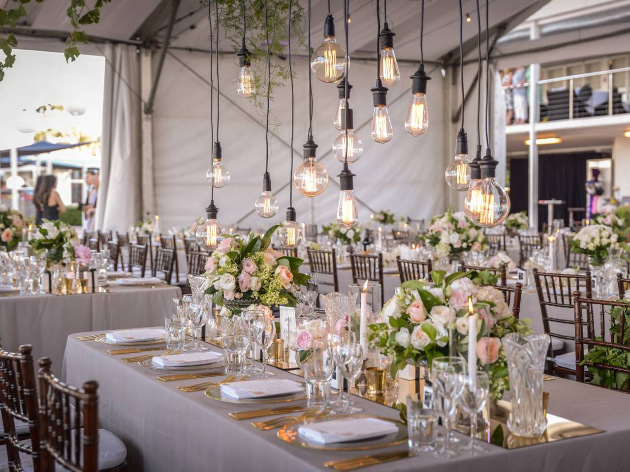 Chairs and Long Tables Wedding Setup With Hanging Lights And Flower Centerpieces