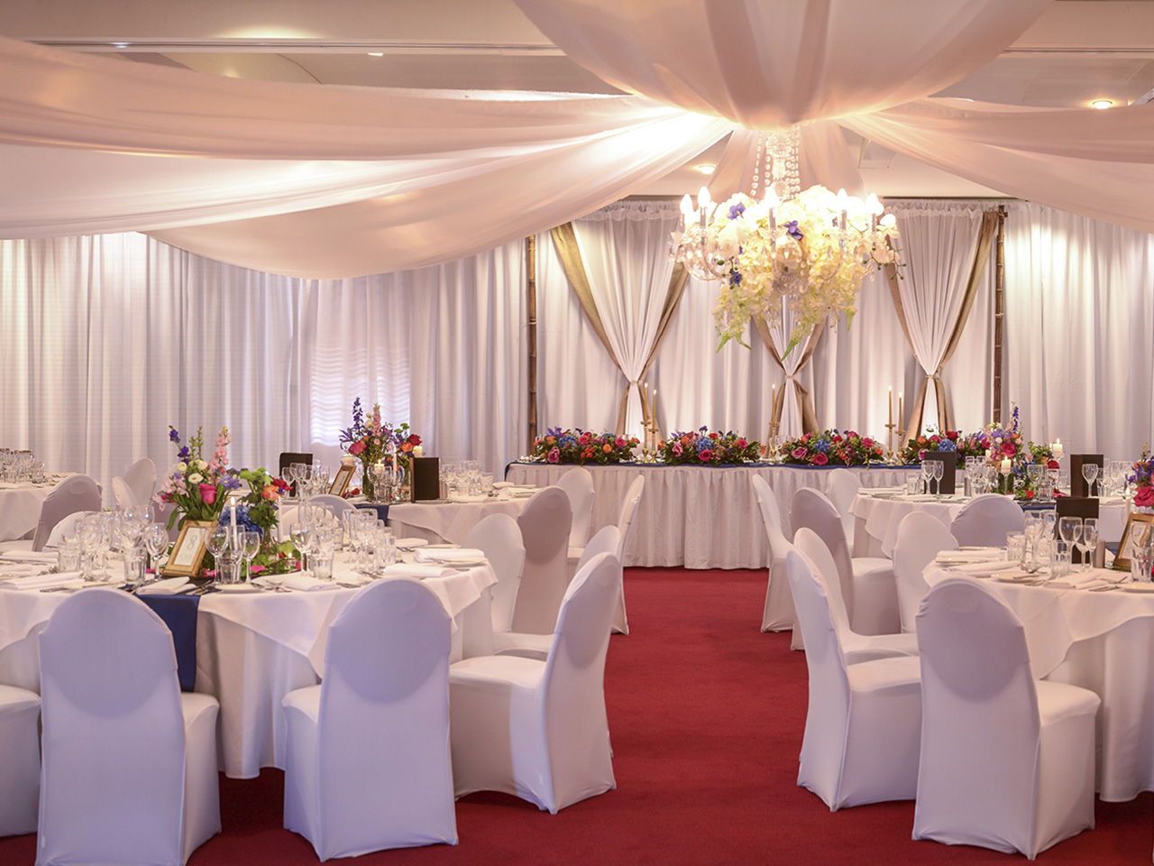 Tables And Chairs In Banquet Style And A Special Long Table With Flower Centerpieces, Chandelier And Ceiling Drapping