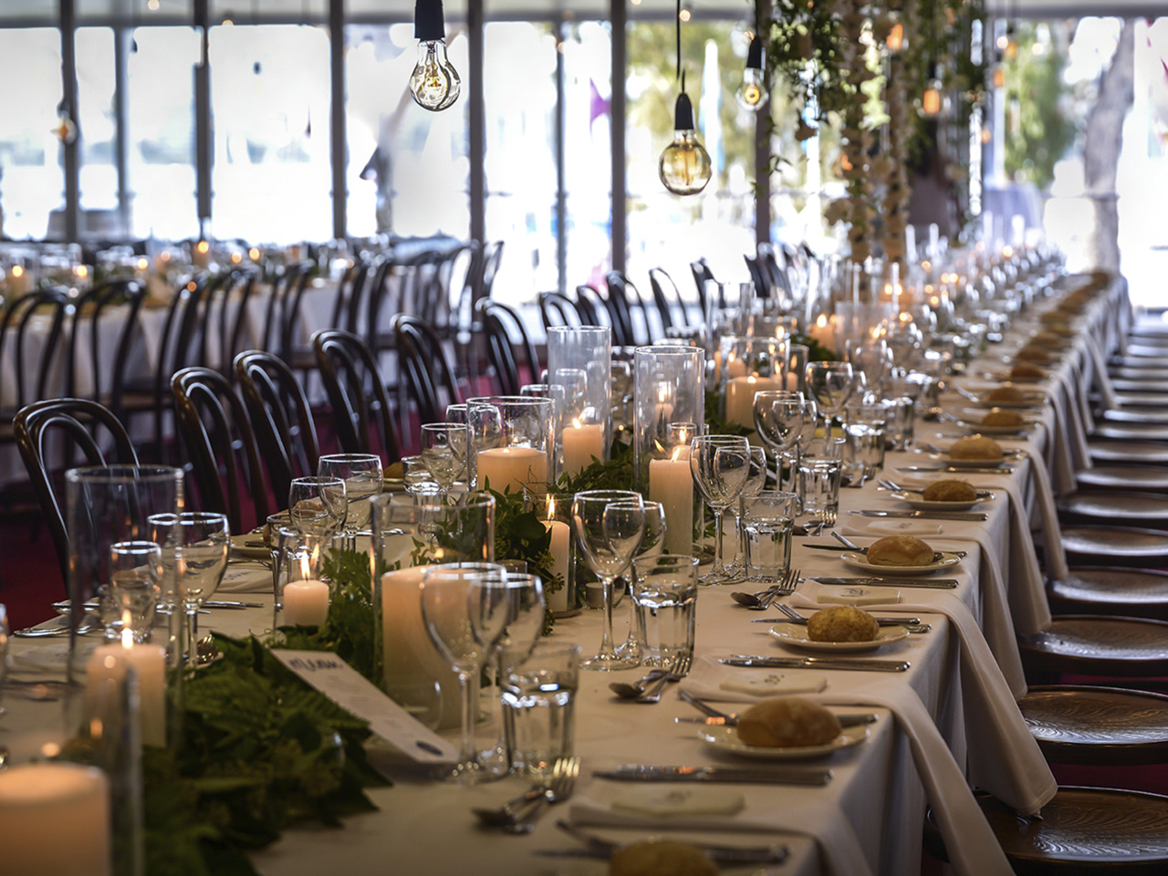 Long Table Setup With Hanging Lights, Candle Lit, Greenery Centerpieces and Wine Glasses