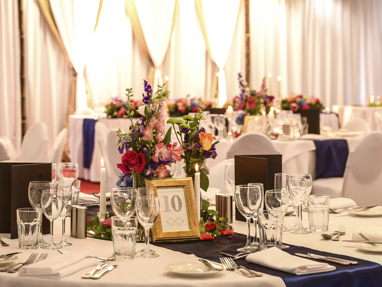 Flower Centerpieces With Table Number, Wine Glasses, Table Napkins, Spoon And Forks And Stage Behind