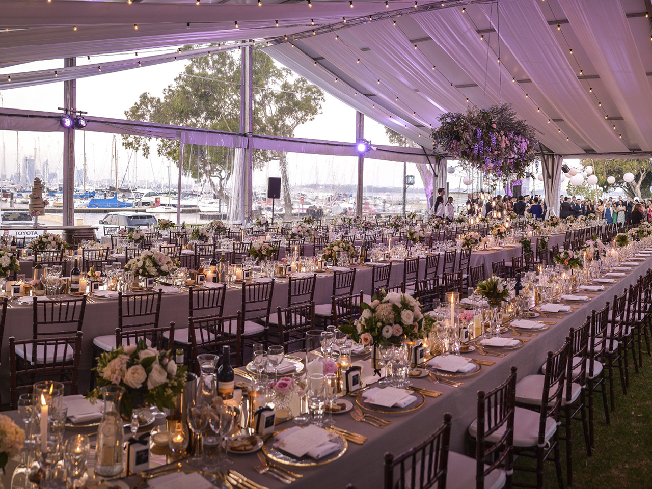 Long Tables with Chairs, Centerpieces, String Lights, Hanging Flower And Ceiling Drapping