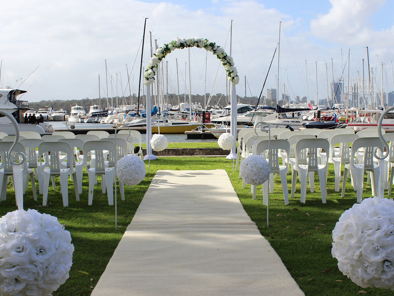 Wedding Ceremony Setup Near The Sea With White Carpet, Flowers, Flower Arc And Boats Behind