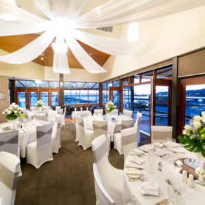 Chairs And Tables In Banquet Style Inside The Function Venue With Glass Windows And Ceiling Draping