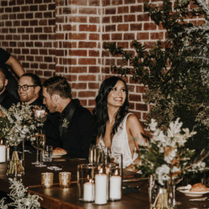 Bride at long table enjoying her special day