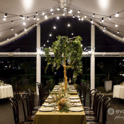 Long Table With Chairs And String Lights Inside The Function Room with window outlook