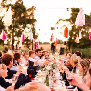Guests Wine Toasting In A Long Table Under The Sky