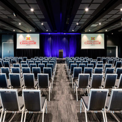 Chairs Setup For A Conference Inside The Function Room With Two Projection Screens And Stage In Front