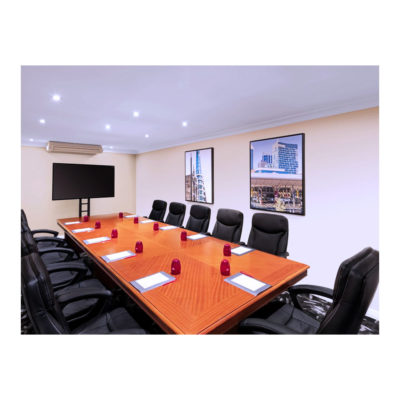 Small boardroom with wooden table and TV
