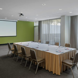 Empty conference room set up with long tables and chairs and projector screen
