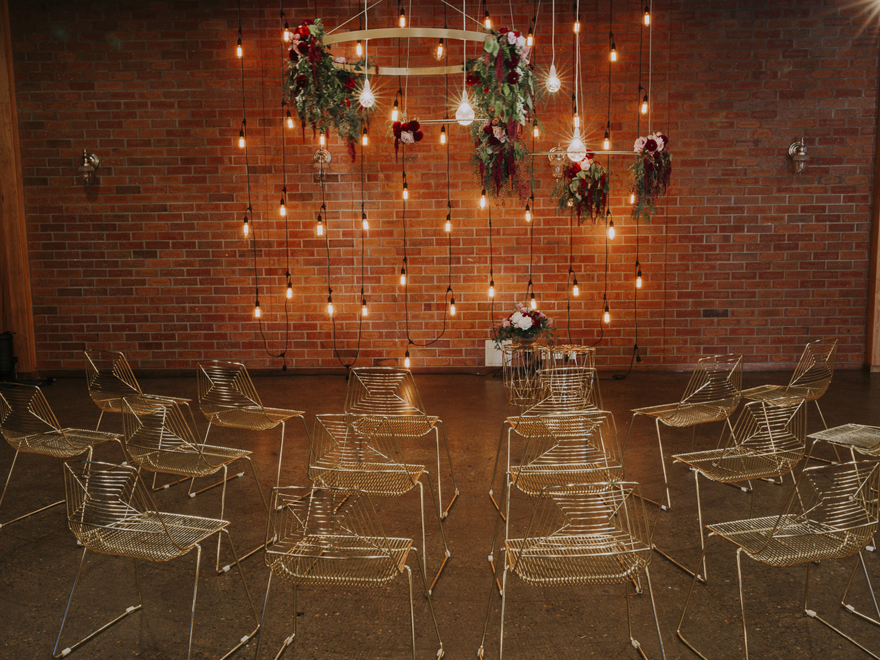 Brick wall decorated with lights with empty wire chairs ready for ceremony