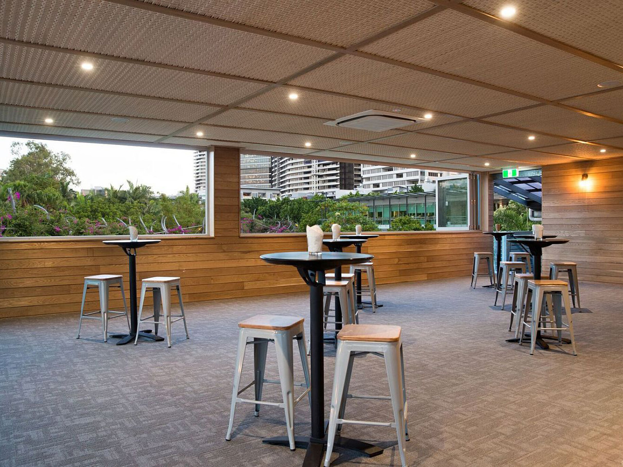 Empty function space overlooking city with round tables and bar stools