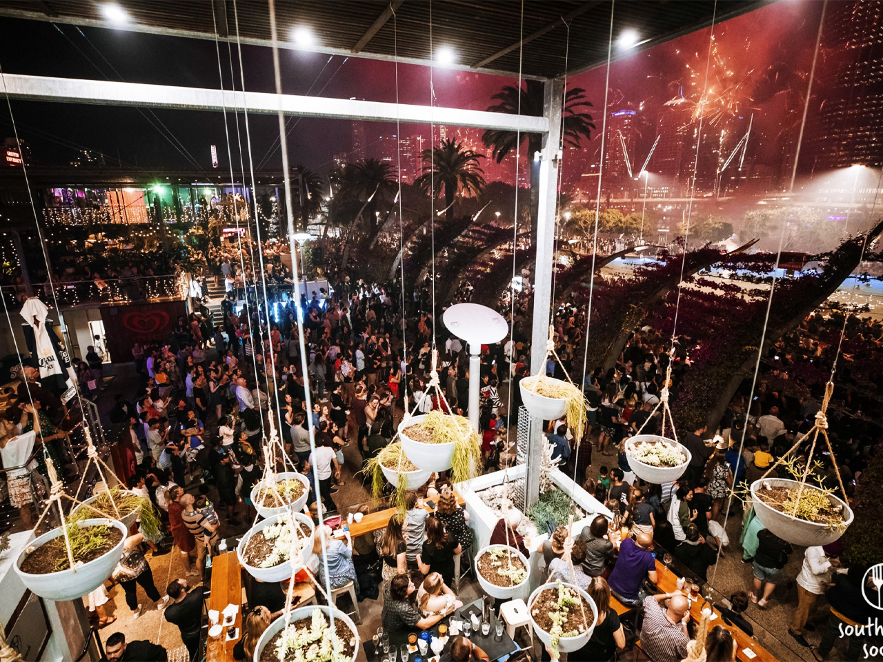 The Lookout venue in the evening with hanging pots and crowd overlooking city with fireworks