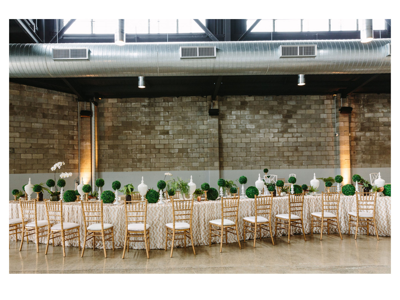 Long tables with black chairs decorated for wedding function